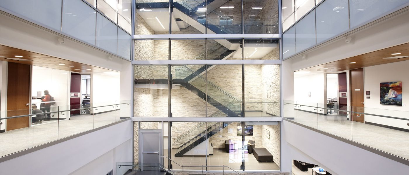 distant view of stairwell visible through glass wall, indoors