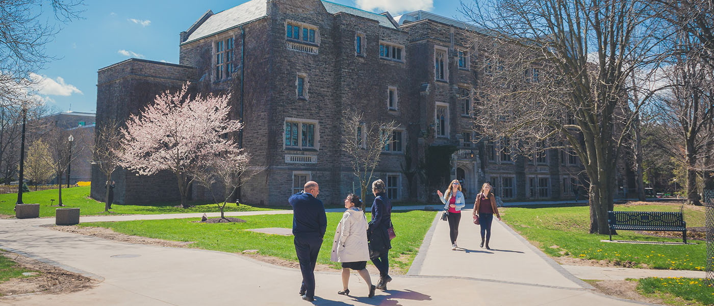 People walk on paths towards a large stone and brick building on campus.