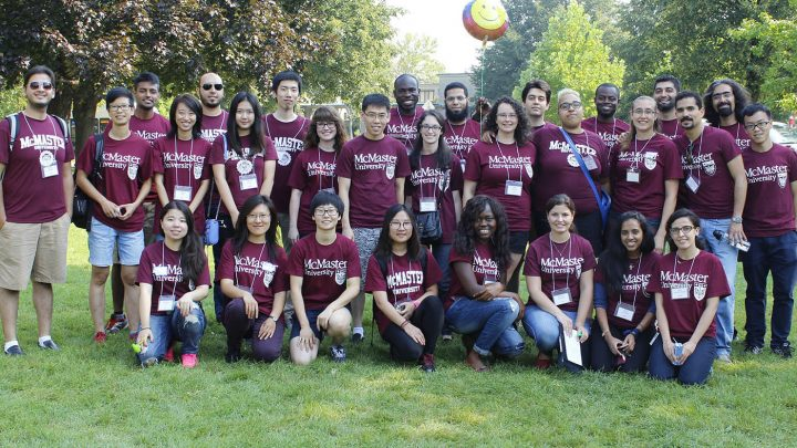 A group of graduate students pose in rows. Each are wearing a McMaster Unversity volunteer t-shirt.