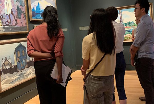McMaster grad students face a wall of paintings at the McMaster Museum of Art.