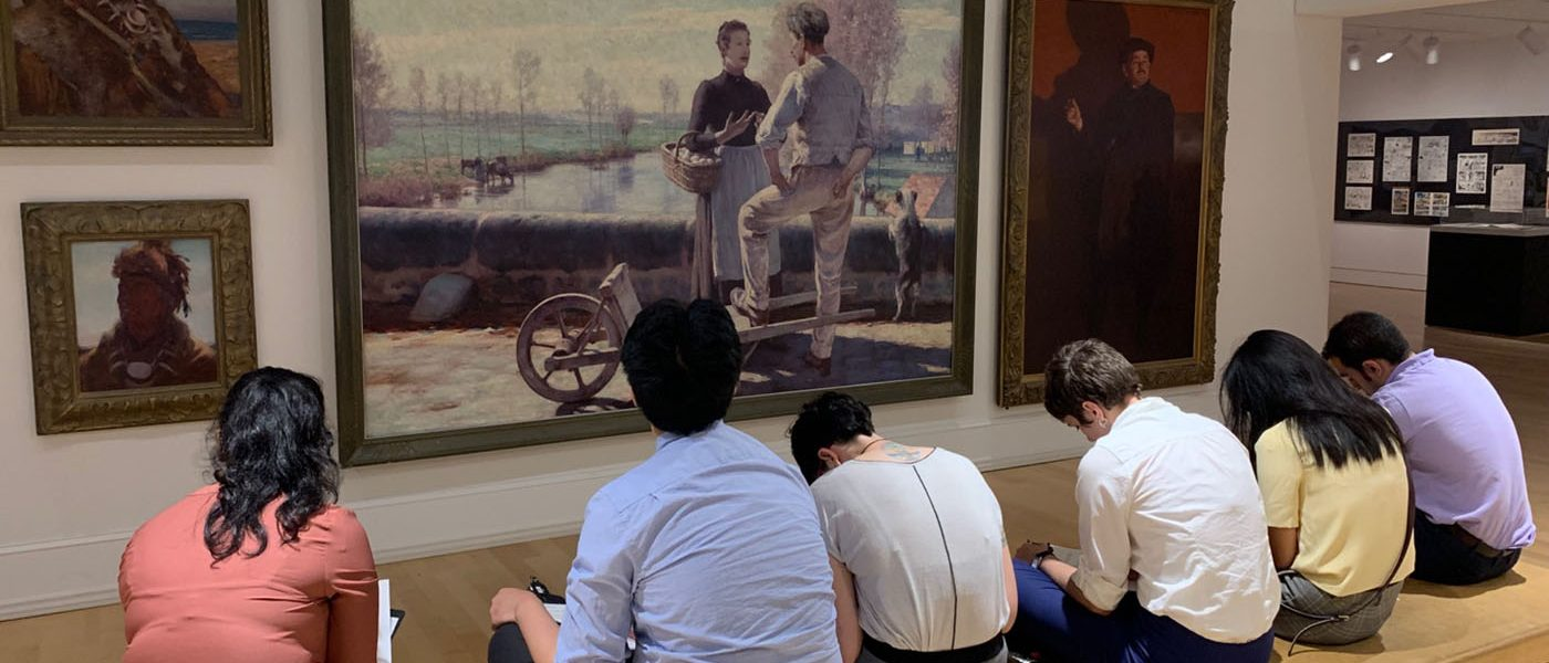 Six students sit on benches, facing a wall of paintings in the McMaster Museum of Art