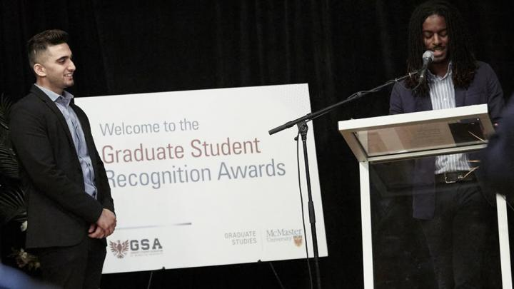 A student speaks at a podium as another student stands to his left.