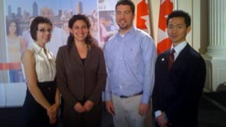 Two women and two men stand side by side as they smile at the camera.