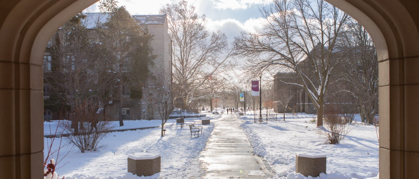 Looking at campus from the archway between Gilmour and University halls. The sun glistens off snow and a cleared path.