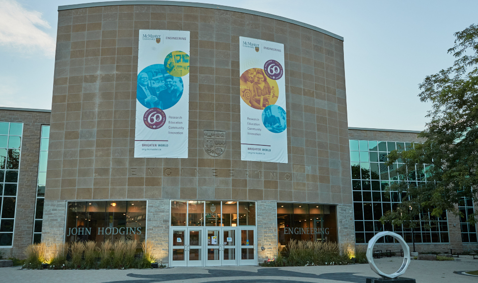 Two large banners hang across the front of the John Hodgins Engineering building,
